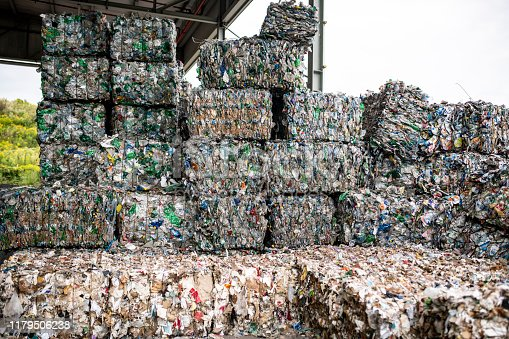 Close-up of compressed paper and plastic gathered into bundles and stacked outdoors at waste management facility.