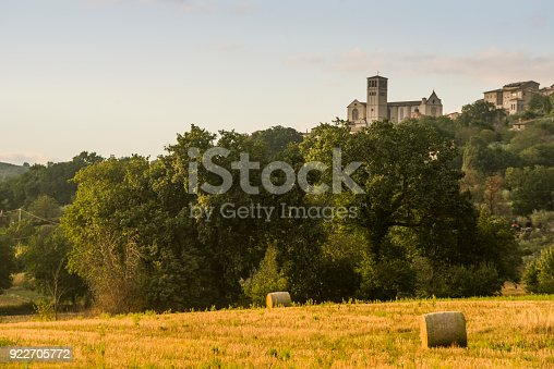 Bales of hay in a field in front of Assisi' s cathedral, Umbria, Italy