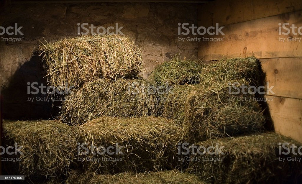 Bales of hay in a stone and wood barn stock photo