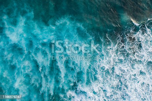 Aerial shot of big ocean waves hitting a coral rif.