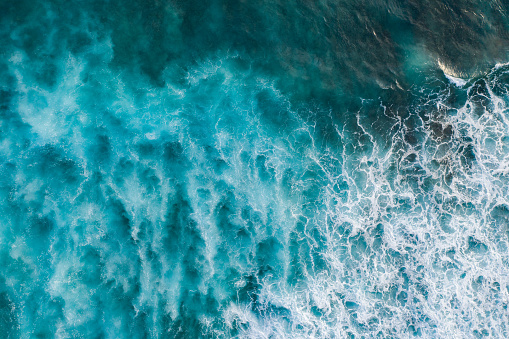 Bali, aerial shot of the turquoise ocean surface with waves.