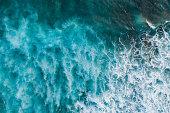 Aerial shot of big ocean waves hitting a coral rif.