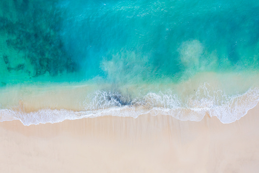 Aerial shot of white sand beach and turquoise ocean on Bali. View from above.