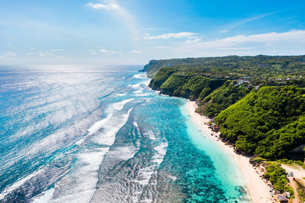 Bali, beach scene from above - blue ocean and rocky hills, covered with tropical trees. stock photo