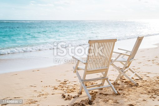 Two white chairs on the beach. Blue ocean and clear sky on the background. Shot taken on Bali.