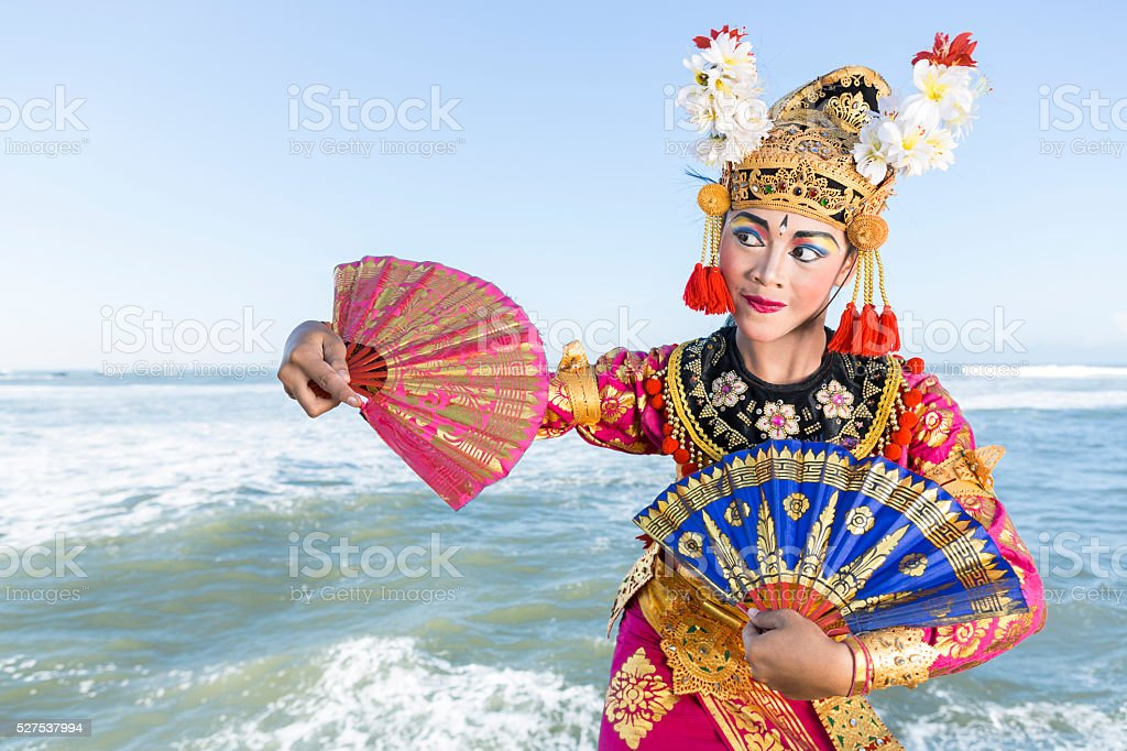 Bali female dancer in traditional costume with fans on beach stock photo