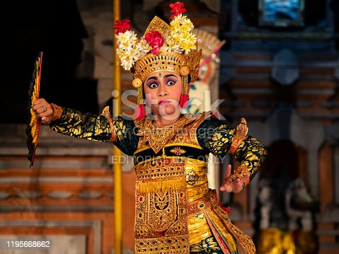 Bali, Indonesia - May 21, 2019: Balinese dancer performing ritual Legong dance wearing traditional costumes during open air ceremony at Pura Saraswati Temple in Ubud, Bali, Indonesia.