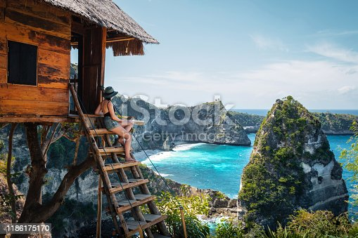 Bali, Indonesia, traveler on tree house at Diamond Beach in Nusa Penida Island.