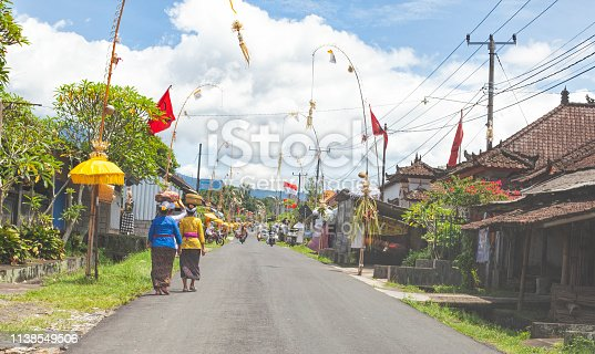 Bali streetscene with traditional decorations. A paved street in the south of Bali with people walking along and traditional houses and umbrellas, flags and straw decoration. Blue sky with some white clouds