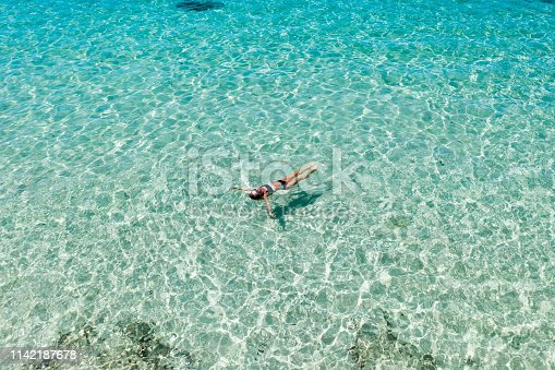 istock Bali, woman floating in transparent turquoise sea. Aerial drone shot. 1142187678