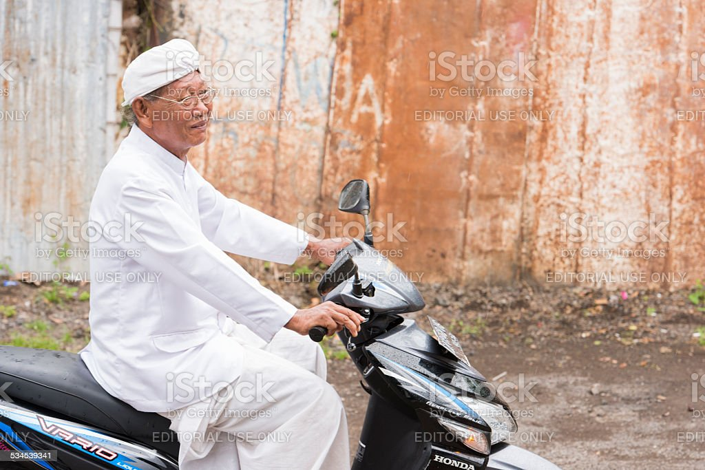 Balinese Hindu Priest Rides to Traditional Ceremony stock photo