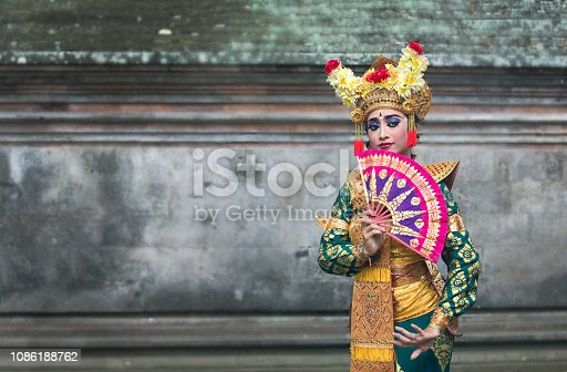 close up of balinese legong dancer in traditional makeup and outfit
