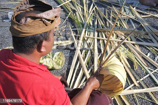 Bali, Indonesia - July 28, 2019:Balinese man preparing Traditional Bali Penjor bamboo pole with decoration in a temples in Bali Indonesia on Galungan Kuningan holidays