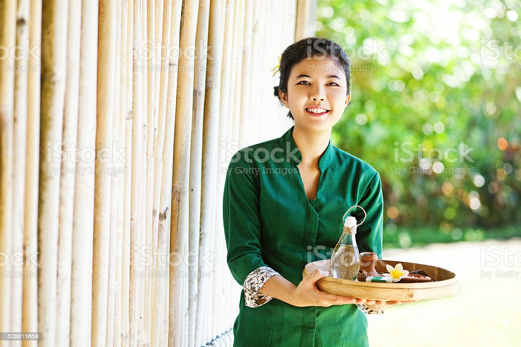 Balinese masseuse with traditional tray and oil stock photo