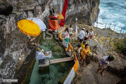A Balinese family prays at a small seaside temple at Peguyangan Waterfall on Nusa Penida, an island located off the coast of Bali. (September 30, 2017)