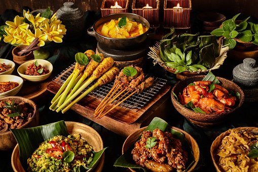 An assortment of Balinese dishes to accompany the steamed rice (not shown). The dishes are Sate Lilit (minced meat satay) and Sate Babi (pork satay), Gedang Mekuah (green papaya soup), Tum Ayam (minced chicken parcel), Udang Goreng (pan-fried prawns), Rempeyek (peanut crackers), Ayam Klungkung (chicken with crushed chili pepper), Lawar Ayam (long bean and chicken salad), Babi Goreng (seasoned pork crisps), and three chili condiments of Sambal Plecing (red chili sauce), Sambal Embe (fried red chili and shallots), Sambal Matah (shallots and lemongrass salsa). A bouquet of Frangipani is used as table decoration.
