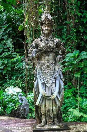 Balinese statue on pedestal. Stone carved sculpture of good god