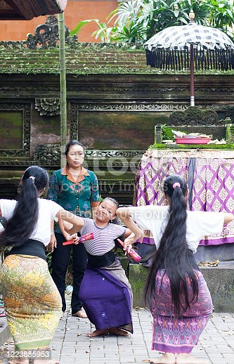 Bali, Indonesia - February 14, 2017: Colour photograph of Balinese Street dance troop practising traditional dance moves in a street in Ubud region.