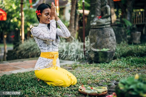 Woman in Prayer Position- offering for Gods. Balinese tradition.