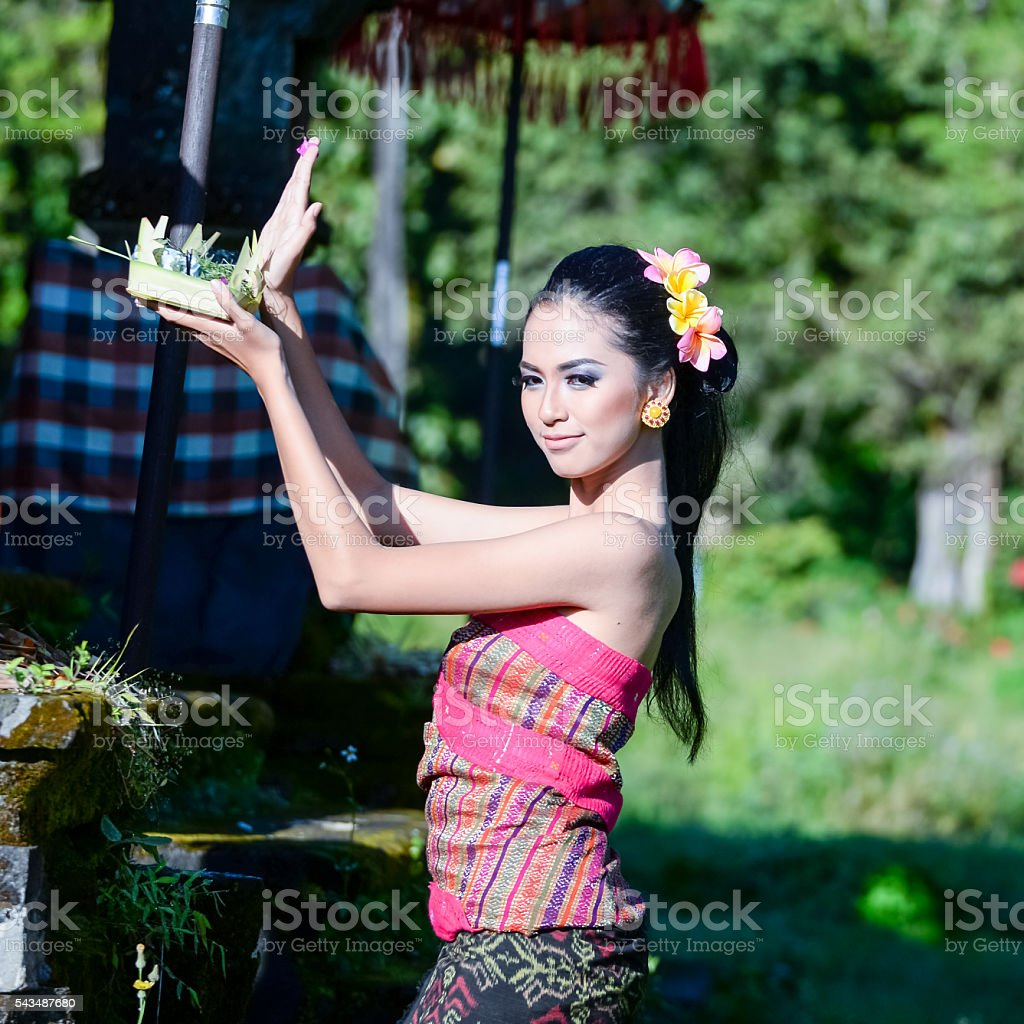Balinese woman in temple with offering for Gods, Bali , Indonesia stock photo