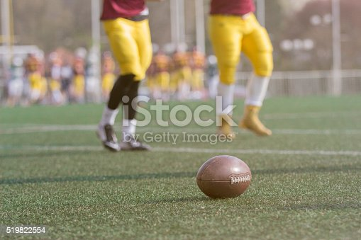 1176737230istockphoto Ball and American football players on the field 519822554