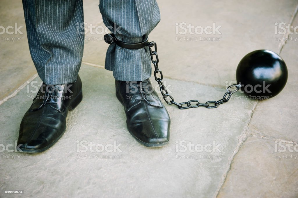 Ball and Chain Businessman Stands on Stone Background royalty-free stock photo