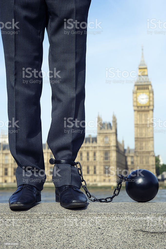 Ball and Chain Politician Stands at Houses of Parliament royalty-free stock photo