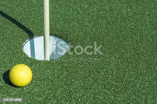 istock Ball at the minigolf just before the putter 1057913880