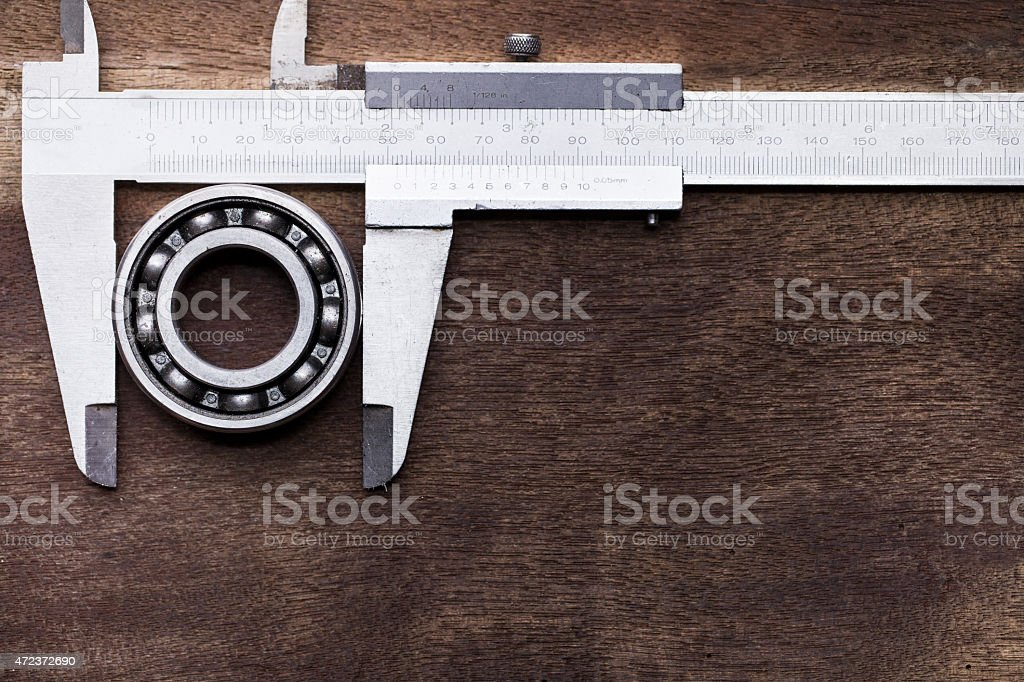 ball bearing and vernier on wooden background stock photo