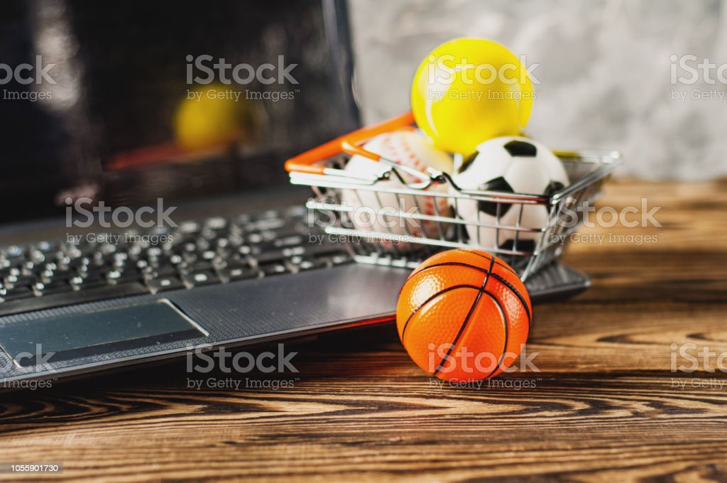 Ball beside sports equipment in market basket on old dirty laptop on...
