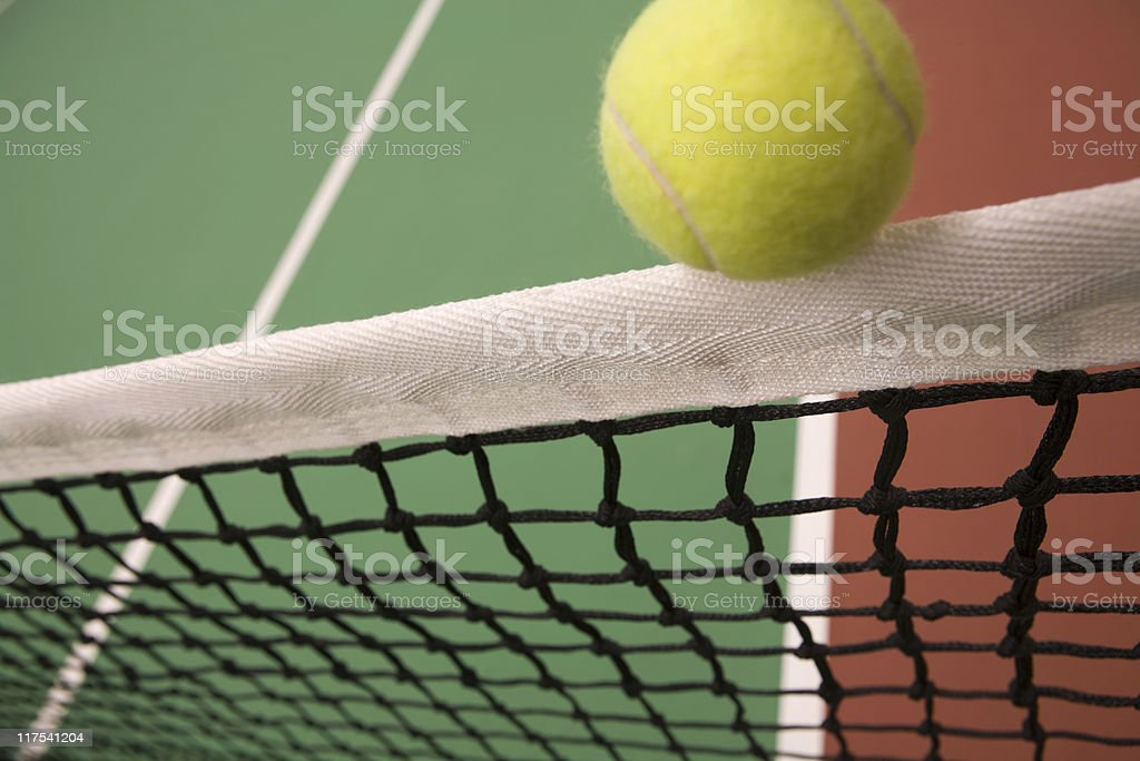 ball bouncing over the net of an indoor tennis court royalty-free stock photo