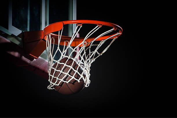 Ball falling through a Basketball Hoop stock photo