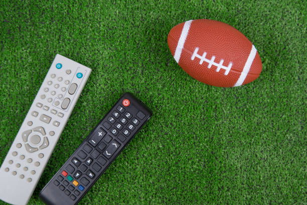 Ball for baseball and remotes from the TV on the green grass Ball for baseball and remotes from the TV on the green grass, Watch the match, live broadcast, championship. Fan. American football political party stock pictures, royalty-free photos & images