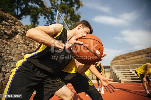 Unrecognizable basketball player holding ball in hands during match outdoor, close up