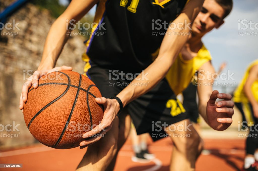 Unrecognizable basketball player holding ball in hands during match...
