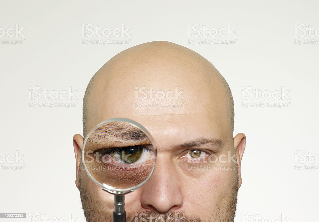 Ball head man Holding Magnifying Glass royalty-free stock photo