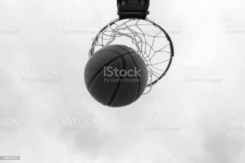 Ball inside basketball hoop, basket against white sky. Outdoor...