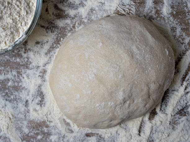 Kugel Brot oder Pizzateig auf einem rustikalen Holzhintergrund mit Staub von Mehl. – Foto