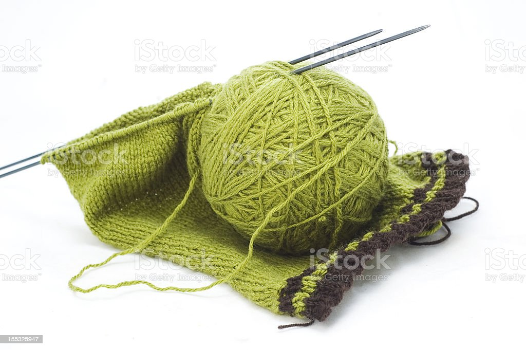 Ball of green yarn and unfinished knitting royalty-free stock photo