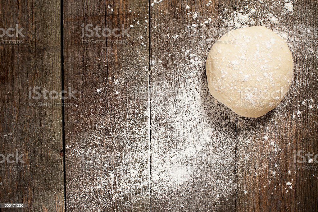 Ball of pizza dough on a rustic wooden background stock photo