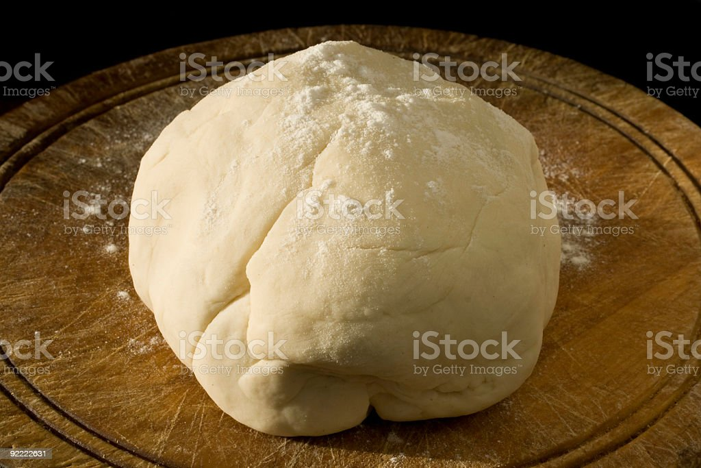 Ball of Pizza dough on wooden cutting board royalty-free stock photo
