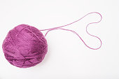 A ball of purple wool for knitting, crocheting isolated on white, violet woolen thread for hobby and DIY.