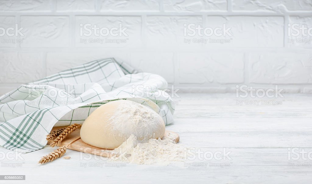 Ball of raw dough isolated on white wooden table with stock photo