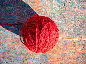 A ball of red woolen thread for knitting. Knitting with needles. A ball of woolen thread. Needlework. Handwork. Hobbies and leisure. Knitted product. Warm clothes. Background image.