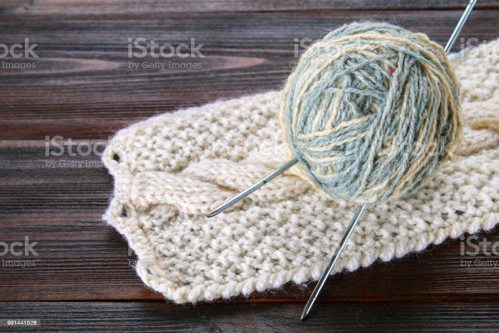Un ovillo de lana con agujas y calcetines de punto en una mesa de madera. Labor de aguja. - foto de stock