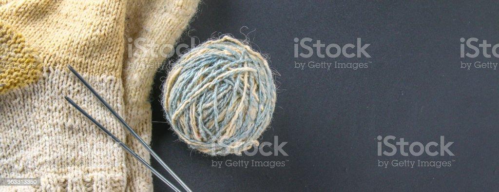 Un ovillo de lana con agujas de tejer y los calcetines en una mesa gris. Labor de aguja. Bandera - foto de stock