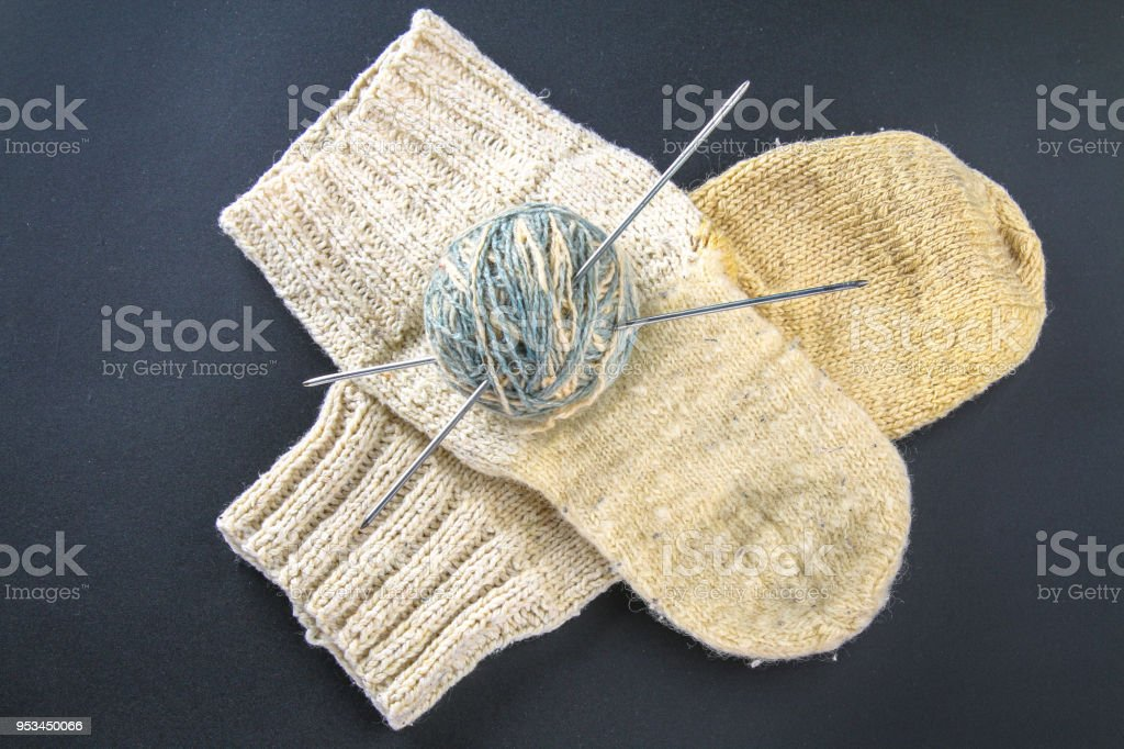 A ball of wool with knitting needles and socks on a gray table. Needlework. stock photo