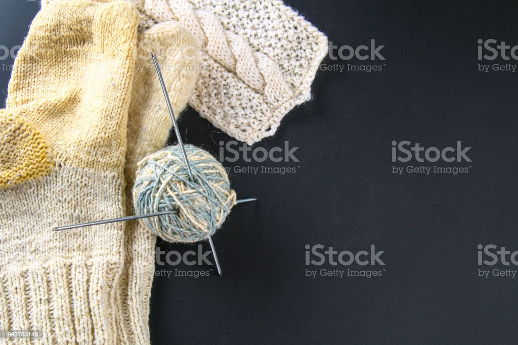 Un ovillo de lana con agujas de tejer y los calcetines en una mesa gris. Labor de aguja. - foto de stock