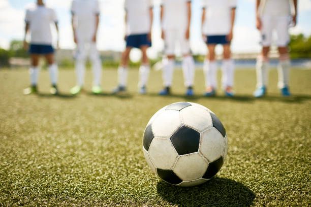 ball on grass in junior football match - soccer league stock pictures, royalty-free photos & images