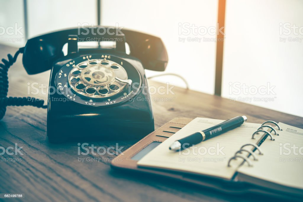 Ball point pen on notebook with old black phone background royalty-free stock photo